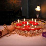 plávajúce maturitné sviečky červenej farby v sklenenej myse s vodou
