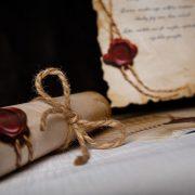 Fotky pergamenu zatočeného do šulku a zviazaného šnúrkou v mašličke.