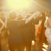 Kreatívna fotka oproti svetlu zo stužkovej slávnosti. Maturant tancuje s mamkou.